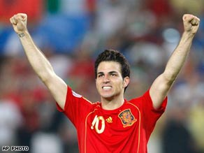 Cesc Fabregas raises his arms in triumph after converting the winning penalty in Vienna.