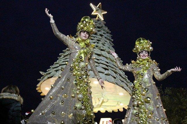 Участницы представления в честь начала рождественского сезона у праздничной ели в Ливане.