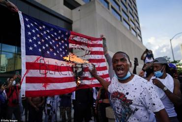 Участник американского Майдана жгет флаг США