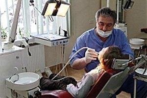 Лікар-стоматолог проводить огляд ротової порожнини дитини