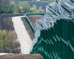 На фотографиях виден длинный забор с колючей проволокой